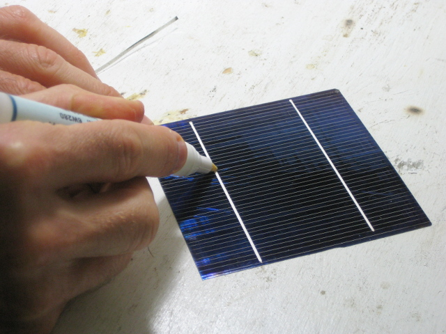 Applying flux using a flux pen to the front of a solar cell for my DIY/homemade solar panel.