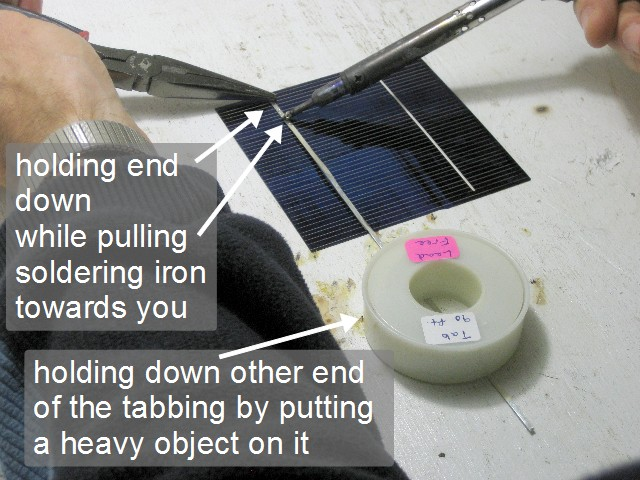 Soldering two solar cells together.