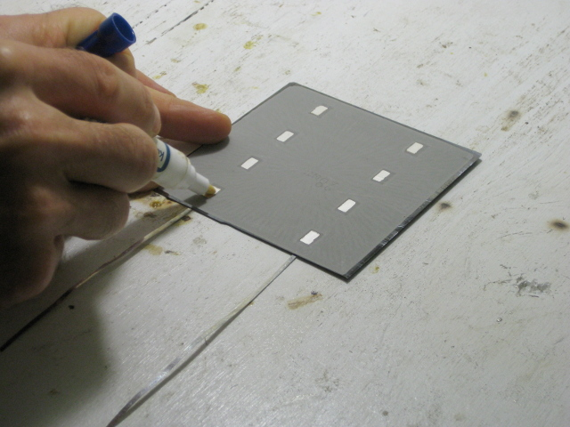 Putting flux on the back of a solar cell before soldering two solar cells together.