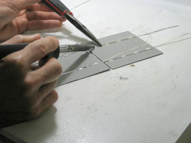 Soldering one solar cell to the next.