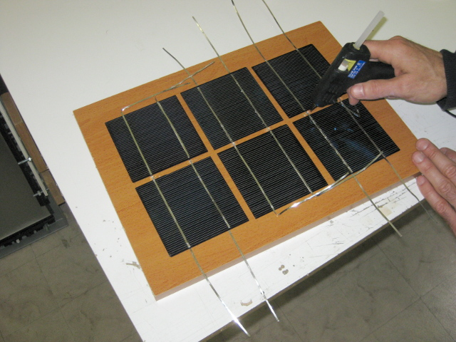 Gluing the solar cells to the wooden backing.