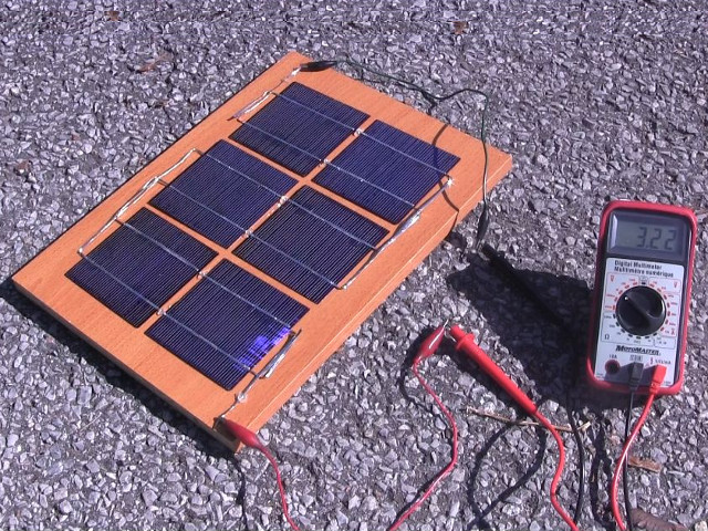 Measuring the solar panel's output using a meter.